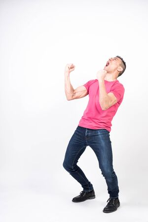 Euphoric man celebrating something. White background. Full body
