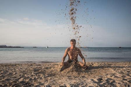 Man kneeling on a beach throwing sand at himself. Formentera island, Spain.