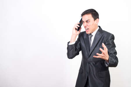 Man in suit talking angry on mobile. White background, medium shot Stockfoto