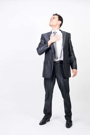Honest man in suit with hand in heart, white background, full body