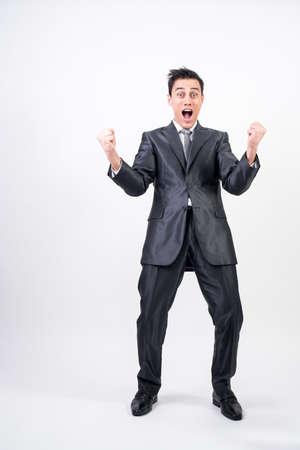 Euphoric man in suit celebrating something. White background. Full body