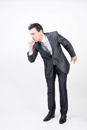 Man in suit coughing. White background. full body