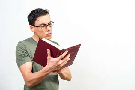 Man with glasses, very concentrated on reading a book. Mid shot. White background. Banco de Imagens