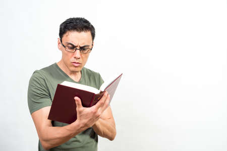 Man with glasses, very concentrated on reading a book. Mid shot. White background.