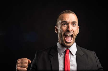 Euphoric man in suit celebrating something. Black background. Close up.