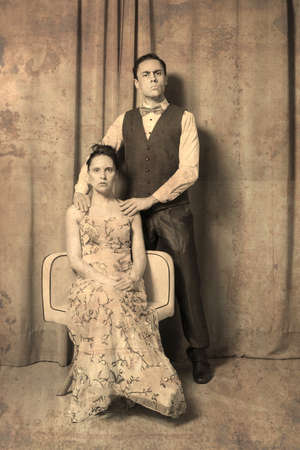 Solemn portrait of Marriage. The woman, seated in an elegant flowered dress. The man, standing, in an elegant suit. Both with serious and solemn expressions. Old photo effect