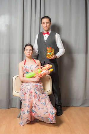 Portrait of smiling and eccentric marriage. The woman, seated in an elegant flowered dress, carrying a toy weapon. The man, standing, wearing an elegant suit and carrying a toy kitten. Full body.