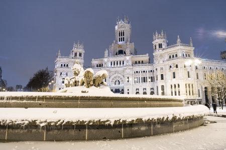 Plaza de la Cibeles in Madrid on a cold winter night after a heavy snowfall.