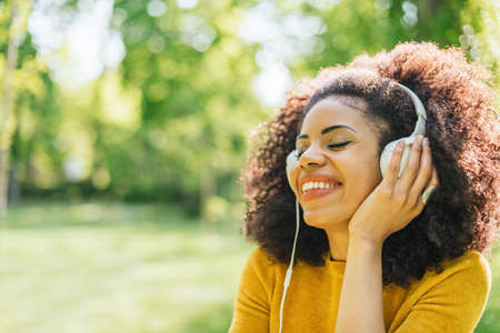 Pretty afro woman listens to music with headphones in a garden.