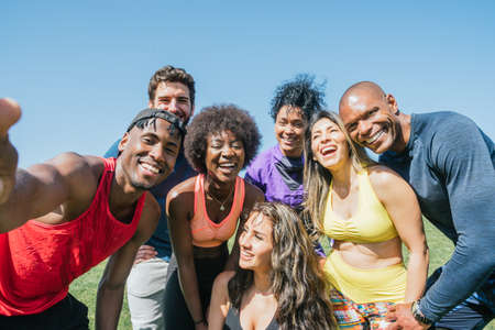 Group of runners taking a selfie in a park. Happy and smiling.