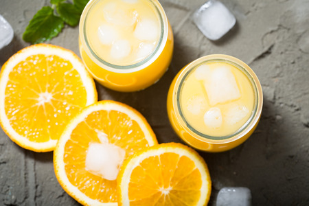 sweet segments: Orange juice in glass with mint, fresh fruits. selective focus, top view Stock Photo