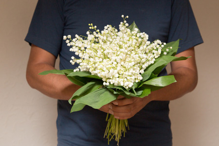 proposes: A man holding a bouquet of lilies of the valley for women. A man proposes Stock Photo