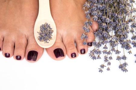 Closeup photo of a female feet with pedicure on nails and lavender. at spa salon. Legs care concept.