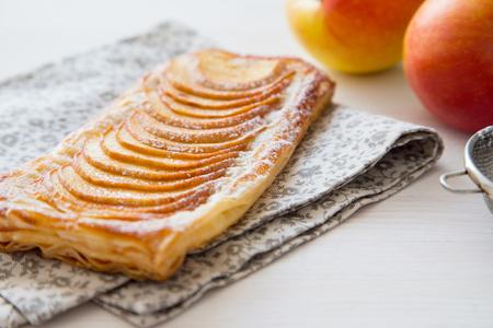 Zelfgemaakte biologische rossige taarten met appels bladerdeeg, klaar om te eten. Heerlijke appelrookwolk op een lichte houten tafel. Apple bladerdeeg op ontbijt, eten, taart.