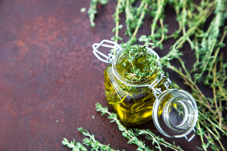 Thyme oil. Thyme essential oil jar glass bottle and branches of plant Thyme with flowers on rustic background. Stock Photo