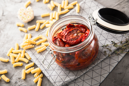 Sun dried tomatoes with herbs and sea salt in olive oil in a glass jar. Stock Photo