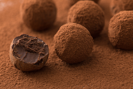 Close up of group of appetizing black chocolate truffles covered in cocoa dust. Shallow depth of field