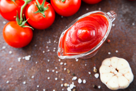 marinara sauce: Tomato ketchup sauce with garlic, spices and herbs with cherry tomatoes in a glass bowl, selective focus.