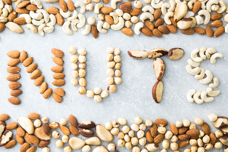 Word NUTS spelled with various nuts on stona background. Assorted mixed nuts.