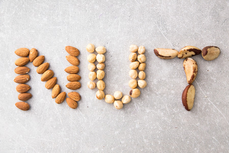 spelled: Word NUTS spelled with various nuts on stona background. Assorted mixed nuts.