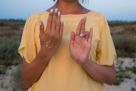hand of a woman meditating in a yoga pose on the beach at sunset.