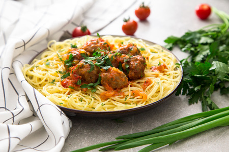 Spaghetti pasta with meatballs and parsley with tomato sauce, selective focus.