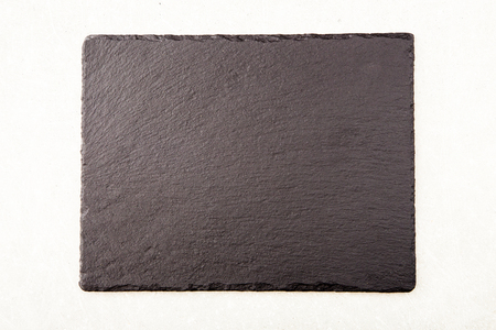 Textured slate board for dishes on light background.