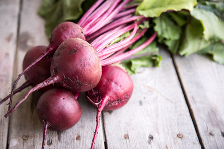Red Beetroot with herbage green leaves on rustic background. Organic Beetroot.