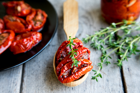 olive green: Bowl of sun dried tomatoes on wooden background. Sun dried tomatoes with olive oil and herbs.