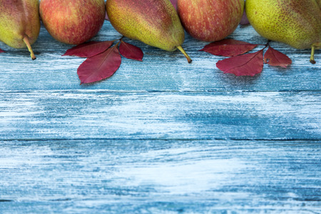 apples, pears and autumn leaves on wooden background. Autumn background.