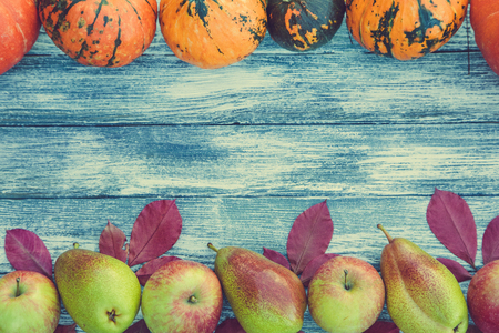 pumpkins, apples, pears and autumn leaves on wooden background. Autumn background. Stock Photo