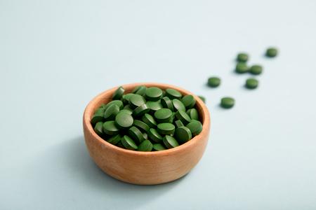 green pills spirulina or chlorella seaweed in the wooden bowl. green barley chlorella.