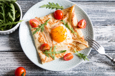 Crepes with eggs, cheese, arugula leaves and tomatoes.Galette complete. Traditional dish galette sarrasin Stok Fotoğraf
