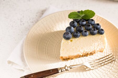 Slice Of Classical New York Cheesecake with blueberries On White Plate. Closeup View. Home bakery concept/