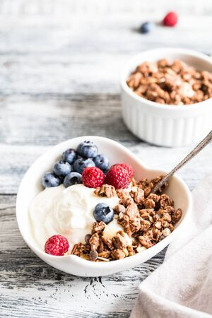 Greek yogurt, blueberries, raspberries and granola in a white bowl on a wooden background.