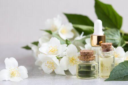 Essential jasmine oil. Massage oil with jasmine flowers on a wooden background.