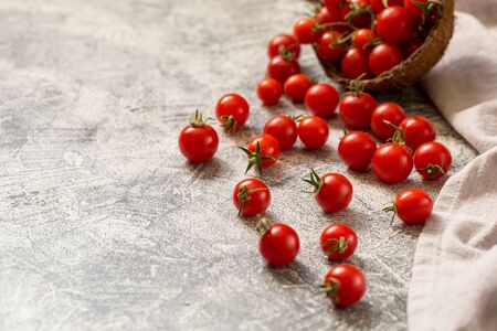 Tiny cherry tomatoes (ciliegini, pachino, cocktail). group of cherry tomatoes on a gray concrete background. ripe and juicy cherry tomatoes/ Archivio Fotografico - 135144141
