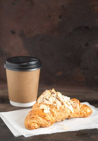 fresh croissant and coffee in a paper cup on a dark background. Foto de archivo - 135401219