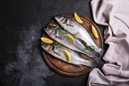 fresh raw whole sea bass. Raw seabass fish with spices and herbs ingredients. Top view with copy space. Stock Photo