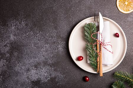 Christmas table with a plate, fork, knife, Christmas tree branches and Christmas decorations. top view, copy space/ Foto de archivo - 136062118