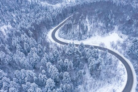 Aerial view of winter road and forest with snow covered trees, top view/ Foto de archivo - 136062132