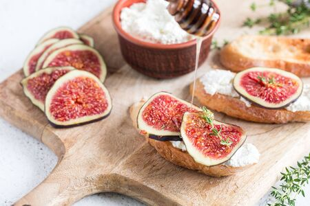 ciabatta or bruschetta with cottage cheese, figs and honey. sandwich with figs and goat cheese. Foto de archivo - 137446866