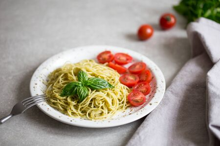 Spaghetti with homemade pesto sauce, basil leaves and  tomatoes Foto de archivo - 137446787