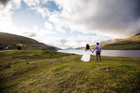 A happy couple in wedding dresses or the bride and groom holding hands and looking at the picturesque nature. Faroe Islands/ Foto de archivo - 138282164