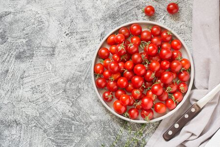 Tiny cherry tomatoes (ciliegini, pachino, cocktail). group of cherry tomatoes on a gray concrete background. ripe and juicy cherry tomatoes/