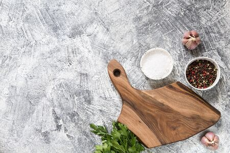 Spices, Herbs, Wooden Cutting board for cooking. Cutting board on grey concrete backdrop. Top view with copy space for text. Menu, recipe mock up, banner background. Reklamní fotografie