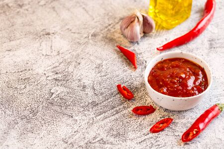 ketchup with hot chili pepper and garlic on a gray concrete background with copy space