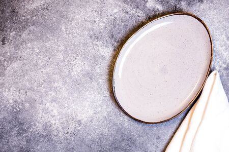 Culinary background with empty plate and napkin on a grey slate, stone or concrete table.Top view with copy space Foto de archivo - 140397698
