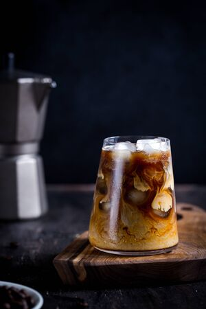 cold late coffee drink with ice. Ice coffee on a wood table with cream being poured into it showing the texture/ Foto de archivo - 139978461