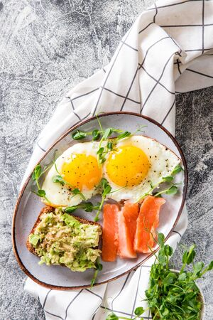 Egg breakfast. Healthy nutritious breakfast with eggs, salmon, avocado sandwich and sprouted pea seeds. Foto de archivo - 140555933